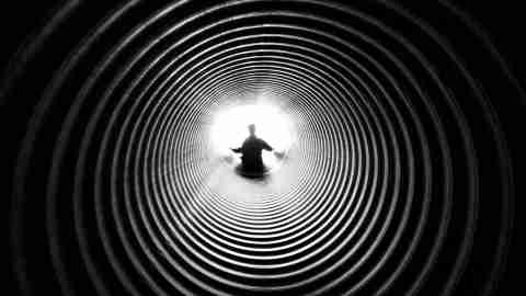 A boy with autism sitting alone in a tunnel