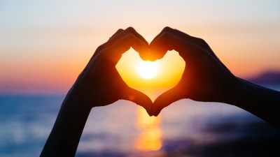 hands forming a heart shape with sunset silhouette. Copy space text.