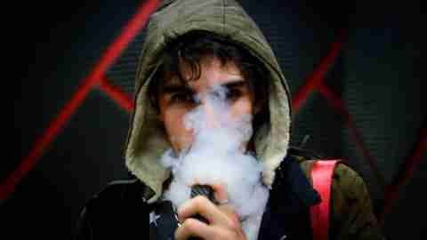 teenage boy vaping with face partially covered from smoke