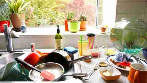 A cluttered, disorganized kitchen sink and counter