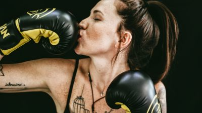 woman kissing a black boxing glove she is wearing