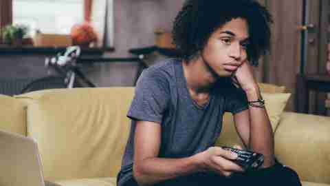 Young African man holding remote control and looking bored while watching TV on the couch at home
