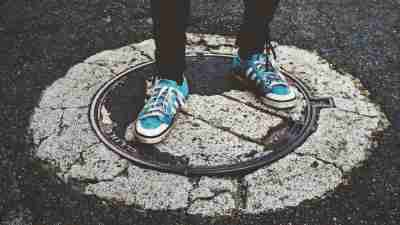 High school student with ADHD standing on manhole cover