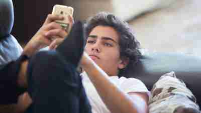 A male teen laying on the couch and on his phone