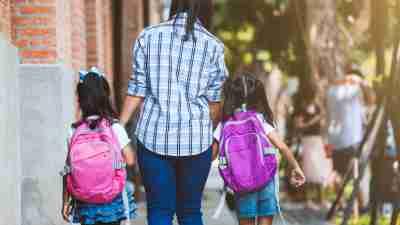 Back to school. Asian mother and daughter pupil girl with backpack holding hand and going to school together