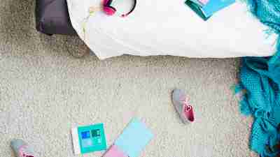 messy bedroom - Directly above view of teen girl's messy bedroom with blanket, sneakers and school books scattered on carpet