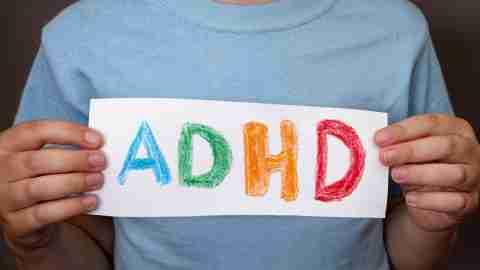 """Young boy holding a hand-drawn """"ADHD"""" sign."""