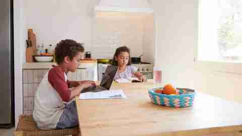 Children doing homework on the kitchen table