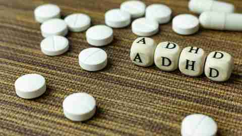 "Lettered dice arranged to spell ""ADHD"" with generic medication pills around"