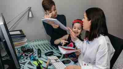 Woman working from home with her children coming up to her with school work