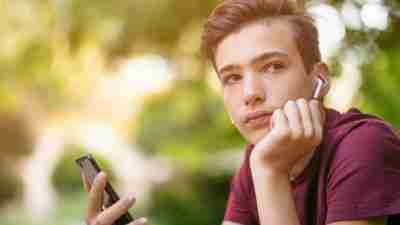 Close-up portrait of a thoughtful unhappy teenage boy with smartphone, outdoors.  Sad teenager with mobile phone looks away, in the park.  Pensive teenager in casual clothes with cell phone in park