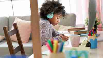online learning - a child wearing headphones as she works at her desk.