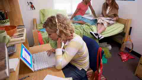 Three young women studying in student dormitory, one at desk