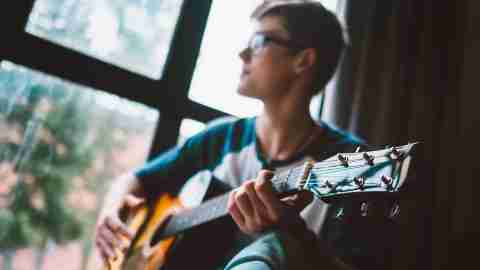 Young man plays on guitar sitting near the window