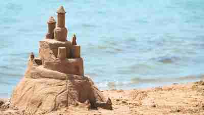Built House sand castle on the south shore of the sandy beach blue sea