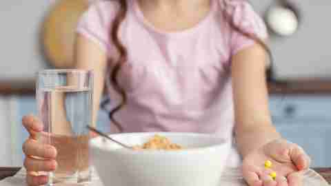 Girl taking her ADHD medication with breakfast