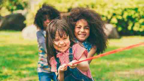 Happy adhd children playing tug of war and having fun during summer camping in the park. Children recreation concept.