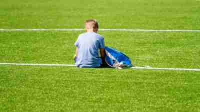 Sad alone adhd boy bullied with backpack sitting stadium outdoors.