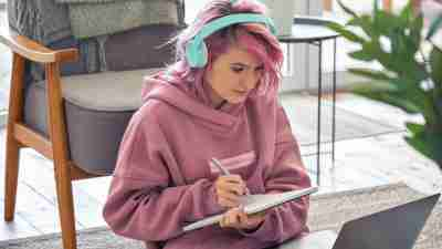Focused adhd hipster teen girl school college student pink hair wear headphones write notes watching webinar online video conference calling on laptop computer sit on floor working learning online at home.
