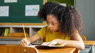 African American school girl sitting in school writing in book with pencil, studying, education, learning. Female student sitting at desk in classroom writing in notebook in exam.