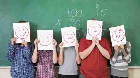 five students holding sheets of paper depicting various emotions in front of their faces