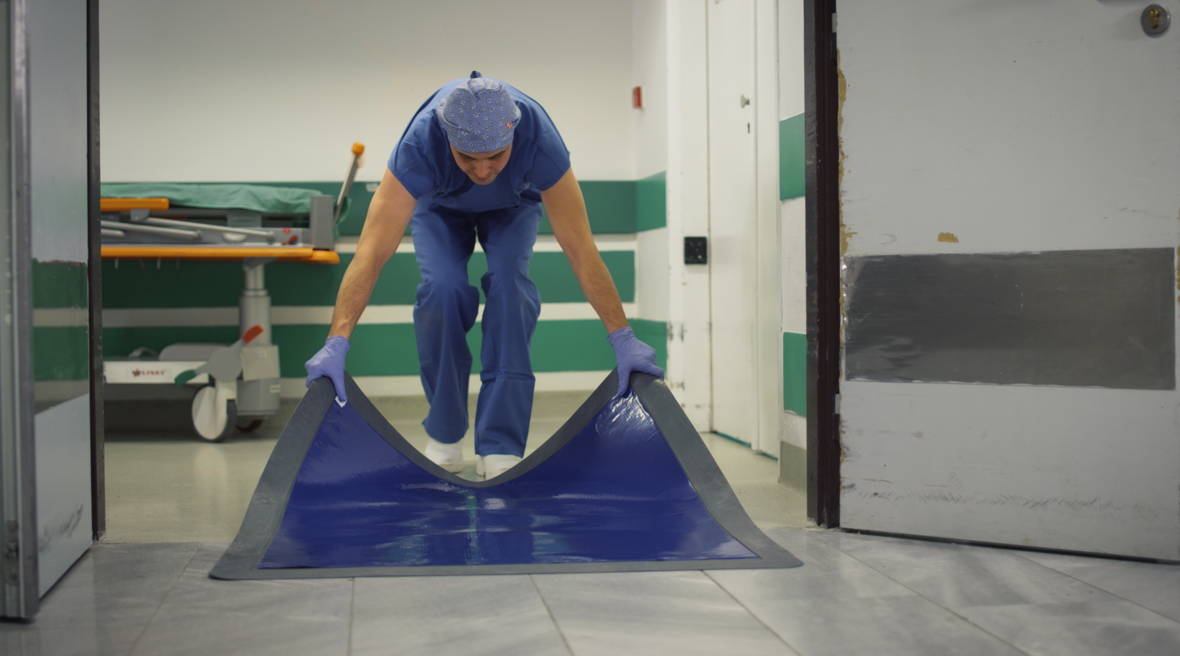 In the picture there is a man who is bent down and he is dragging an adhesive mat in a rubber frame.