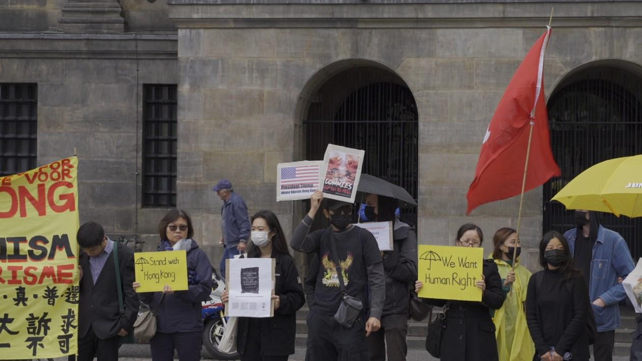 """守护民主荷港同行""""集会现场,与会者手持标语牌支持香港民主运动"""