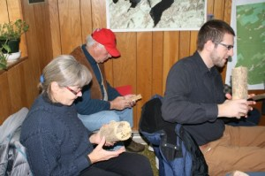 Attendees examine wood samples for the characteristic D-shaped exit hole of the emerald ash borer and the large, round exit hole of the Asian longhorned beetle.
