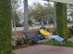 Steve on a swinging park bench on the riverfront