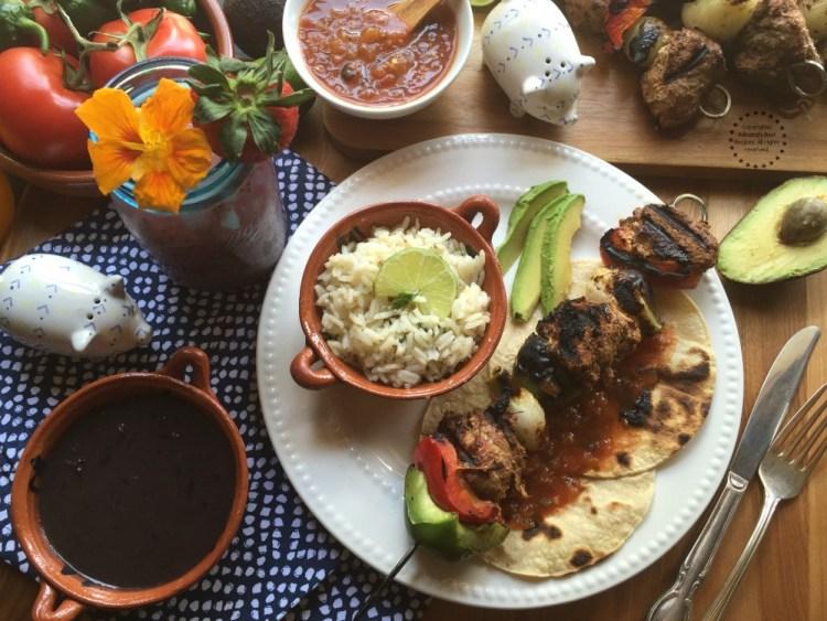 Serve the Chipotle Pork Loin Alambres with cilantro lime rice, black beans, avocado slices, tortillas and salsa