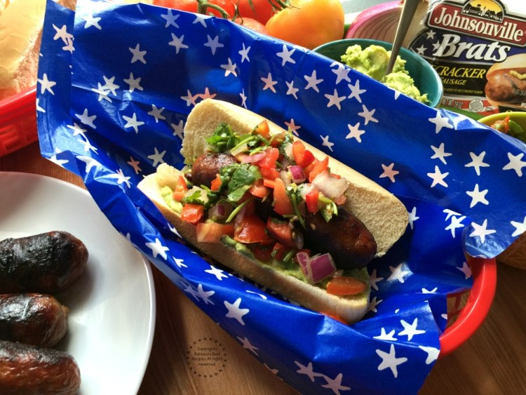 Firecracker Pork Brats garnished with pico de gallo and avocado to add a latin twist to a traditional American dish