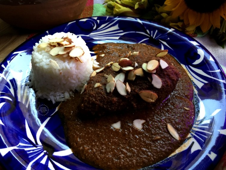 Serving the almond mole over chicken and with a side of rice
