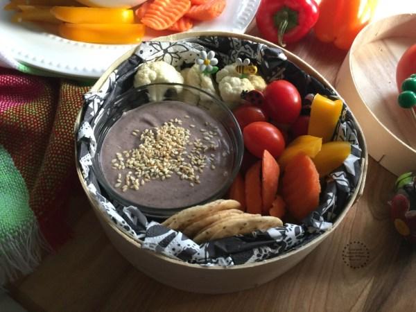 Coloca un poco del humus de frijol en un recipiente y acompaña de verduras y galletas