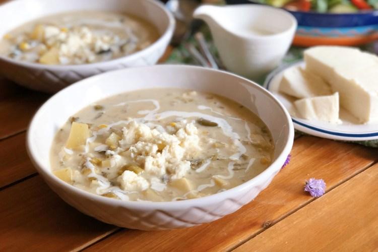 Caldillo de queso fresco con papas servido en un tazón y adornado con más queso fresco y cintas de crema fresca Mexicana
