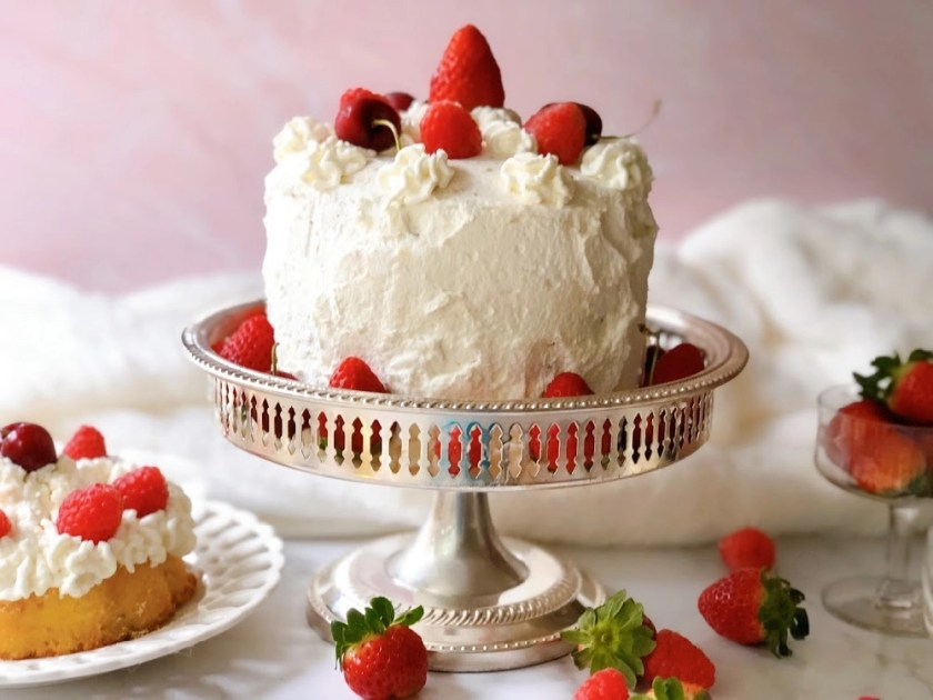 Victoria's Sponge Cake with berries and whipped cream presented on a silver plate