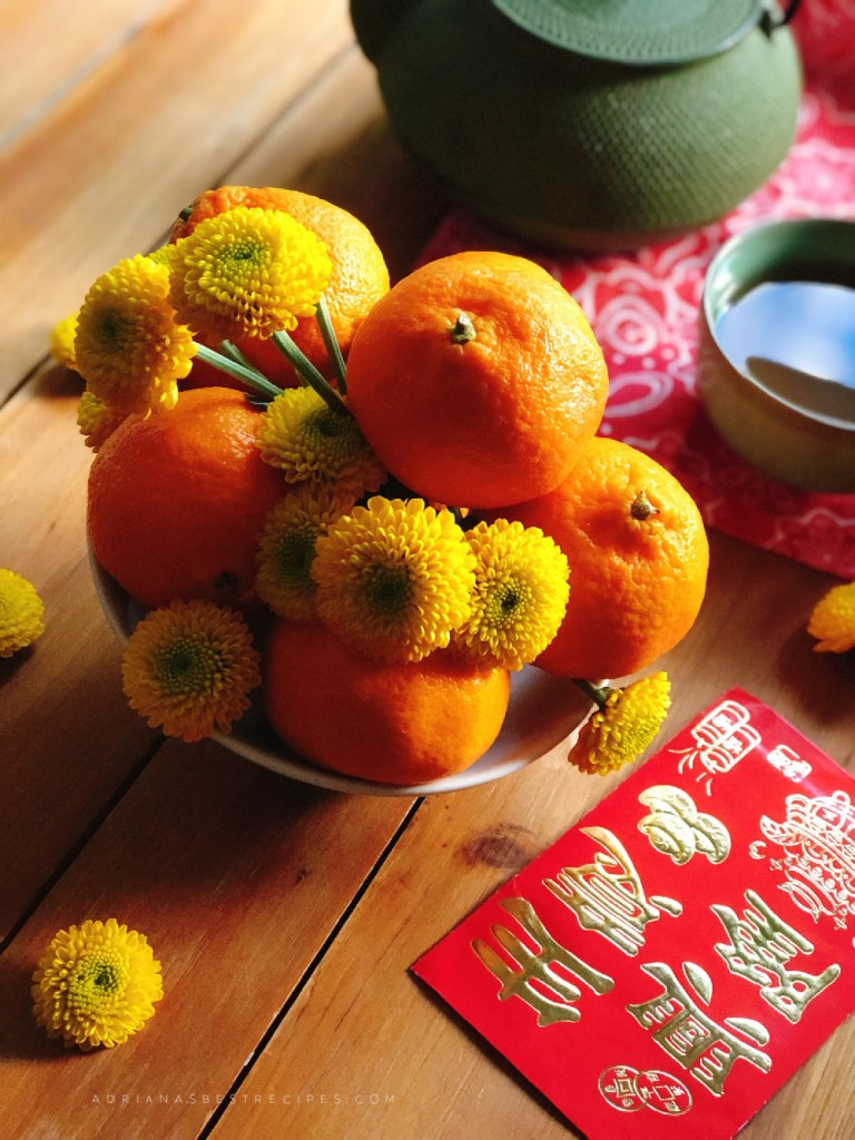 A bowl with yellow flowers and mandarins to attract prosperity in the new year