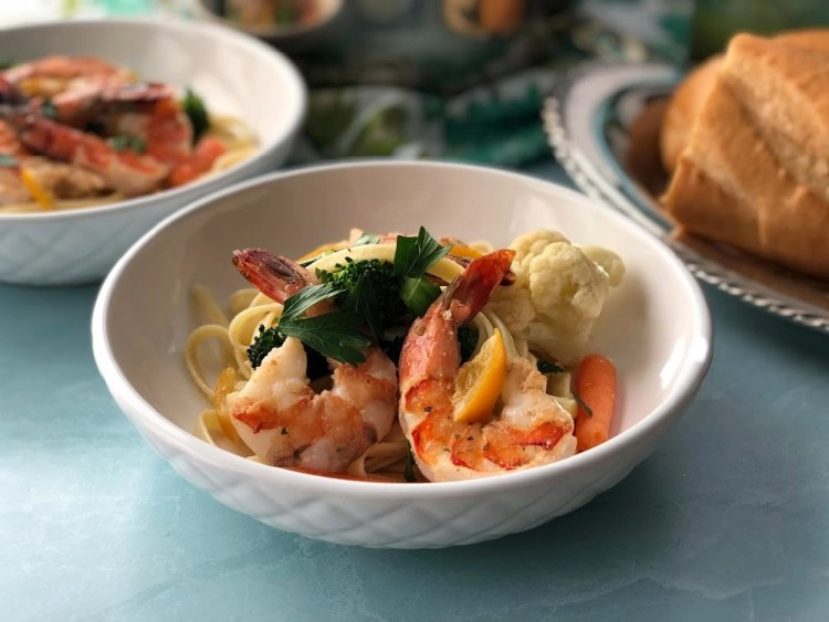 A white bowl with shrimp primavera and colorful veggies garnished with parsley and preserved lemons