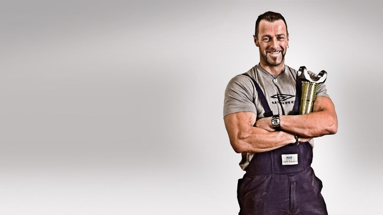 Portrait of muscular man holding metal product against a grey background, wearing a grey Umbra t-shirt and dark blue dungarees, smiling at camera.