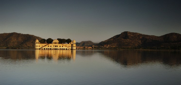 Jay Mahal in the middle of the Man Sagar Lake in Jaipur city, Rajasthan, India at sunrise with a graduated blue sky.
