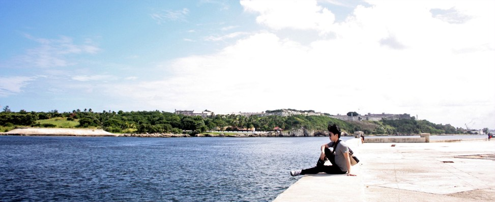 Adrian Lin sits, looking out from the Malecon, Havana