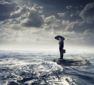 Resilience -- person on a shore with stormy sea and rain holding an umberella
