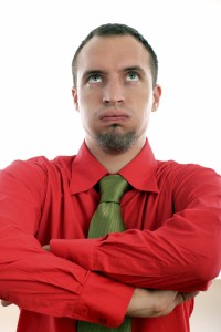 Frustrated man in red shirt with green tie