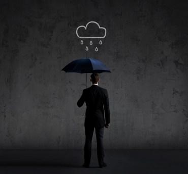 Businessman with umbrella standing under the rain.