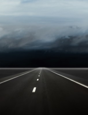 A road leading into a dark, cloudy future