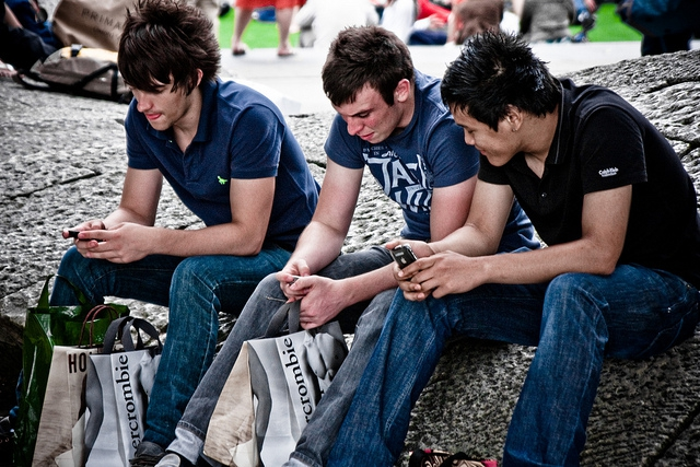 3 men using their mobile phones