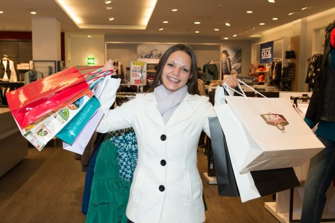 smiling woman holding lots of shopping bags