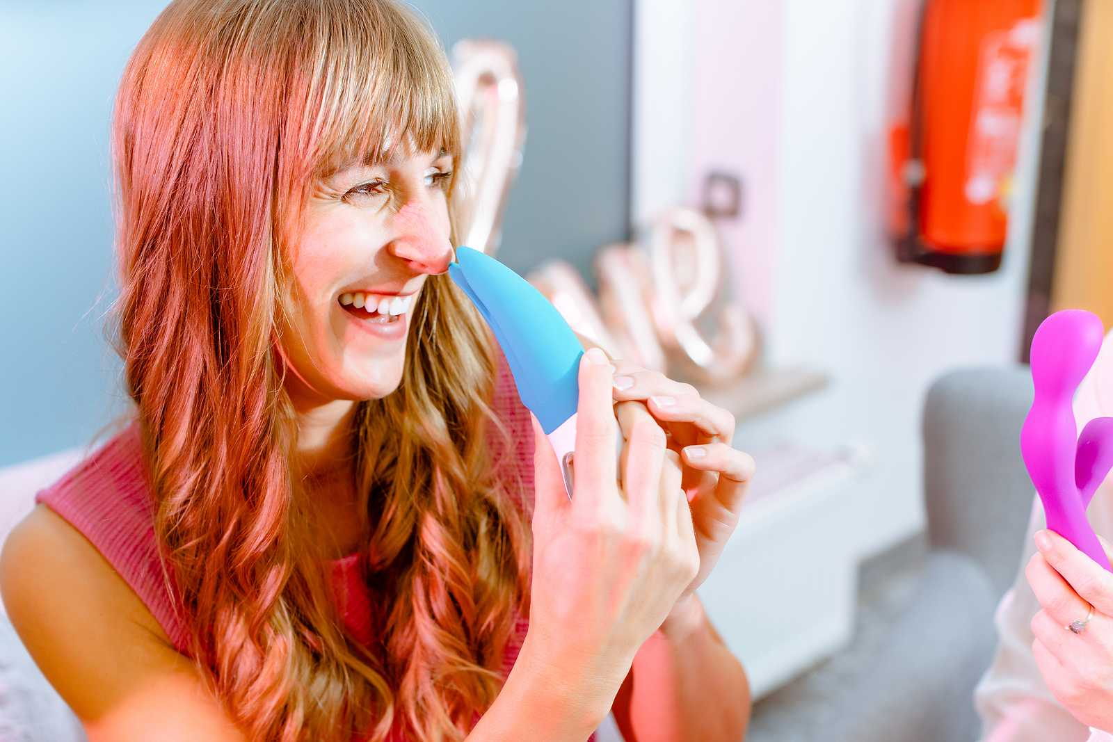 Woman asking saleslady for details of dildo and other adult toys