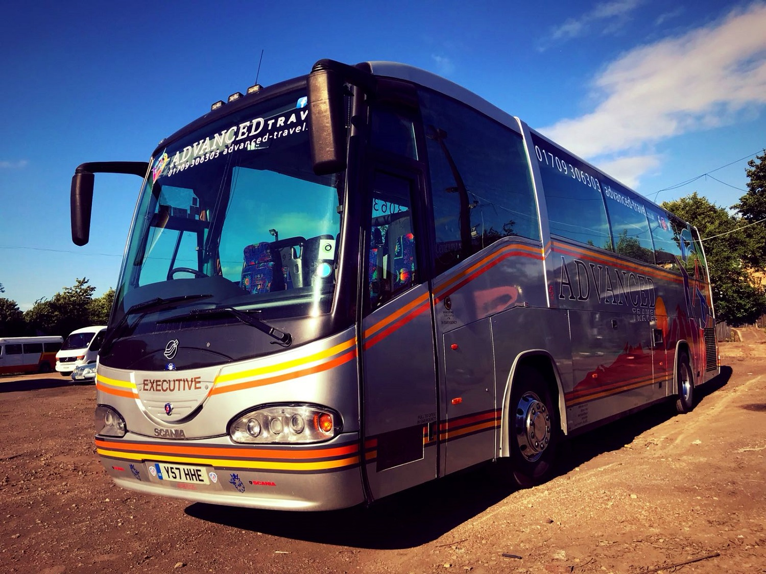A view of the outside of Advanced Travel's 49 seater Scania Irizar coach, which is available for coach hire in Doncaster. The front and left hand side of the coach are visible. The coach is silver with an orange and yellow border. Advanced Travel's name, logo, website and phone number are displayed at the top of the windscreen and also on the side of the coach.