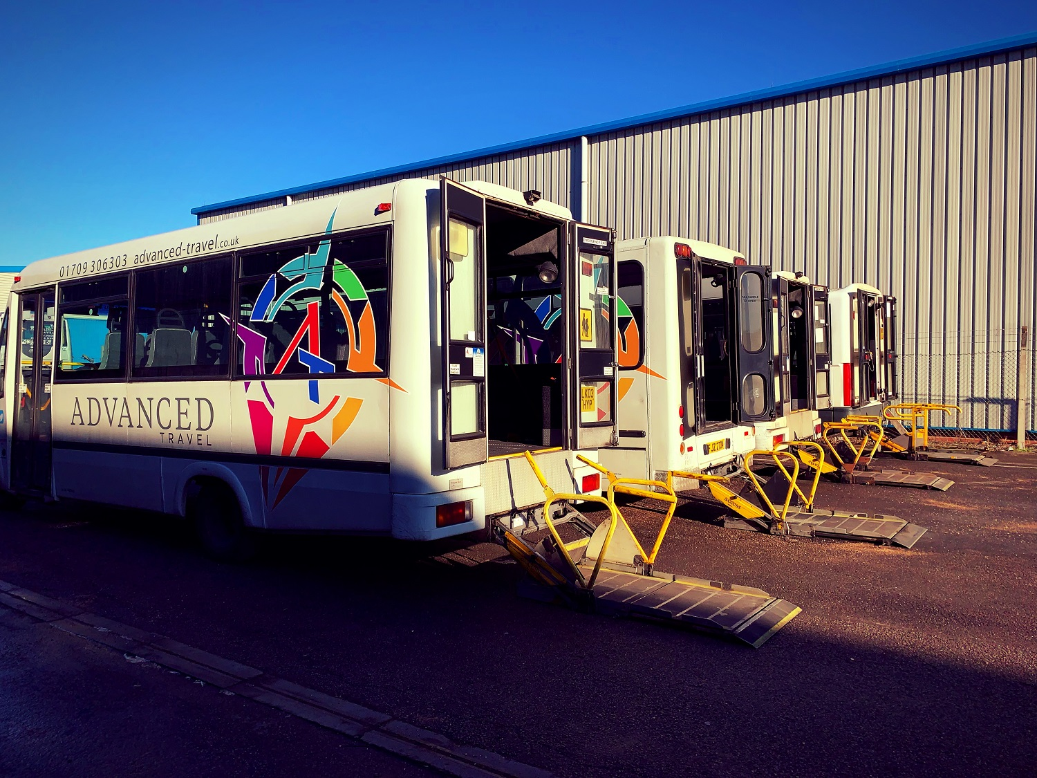 Four of our wheelchair accessible minibuses, shown from the back with their tail-lifts out and ready to take on passengers.