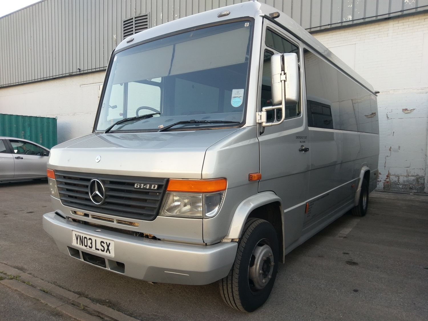 The outside of our Mercedes Vario 24 Seater Minibus. It is silver, has a passenger door on the left side and tinted windows.